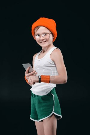 Photo for Smiling boy in eyeglasses and sportswear using smartphone isolated on black - Royalty Free Image