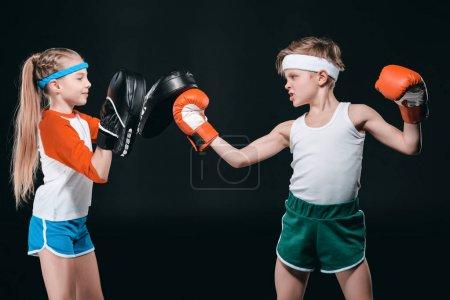 Photo pour Vue latérale du garçon et de la fille en boxe sportive isolé sur noir, concept d'activités pour enfants - image libre de droit