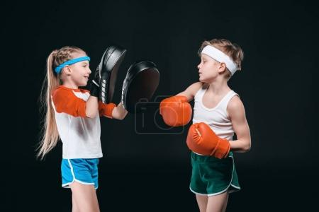 Photo for Side view of boy and girl in sportswear boxing isolated on black, activities for children concept - Royalty Free Image