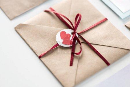 Photo pour Enveloppe avec étiquette avec deux coeurs et ruban isolé sur blanc, concept de carte d'invitation de mariage - image libre de droit