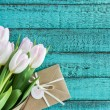Light pink tulips bouquet and envelope on turquois...