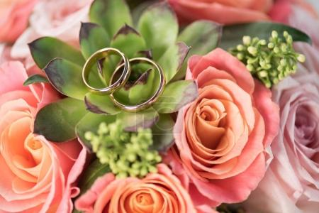 Photo for Two golden wedding rings on bouquet on roses and succulent, wedding rings and flowers concept - Royalty Free Image