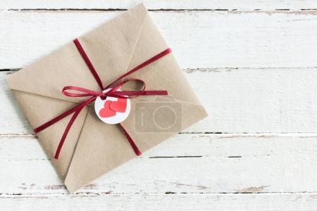 Photo pour Vue de dessus d'enveloppe kraft décorative avec étiquette et ruban sur bois sur table, concept de carte invitation mariage - image libre de droit