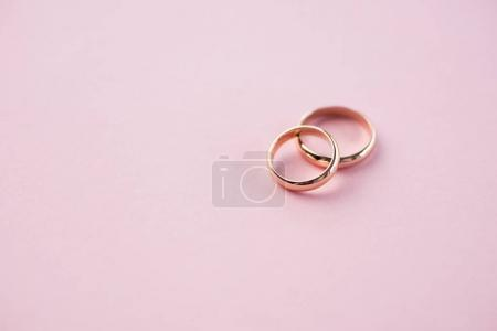 Photo for Close-up view of shiny golden wedding rings on pink, wedding rings background - Royalty Free Image
