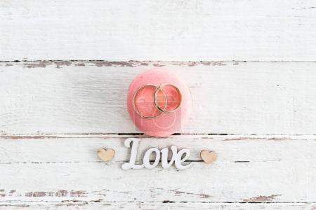 Foto de Vista superior de oro anillos de boda en rosa símbolo de macaron y de amor con corazones - Imagen libre de derechos