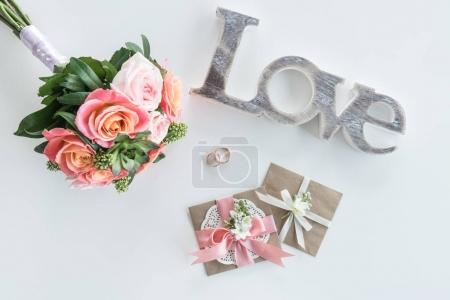 Photo for Top view of golden wedding rings, decorative envelopes, beautiful bouquet and love symbol, wedding invitation card concept - Royalty Free Image