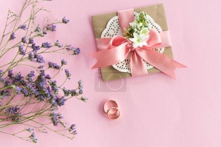 Photo pour Vue du dessus des alliances dorées, enveloppe décorative et belles fleurs sur rose, concept de carte d'invitation de mariage - image libre de droit