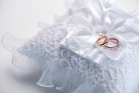 Photo for Close-up view of golden wedding rings on decorative white lace pillow - Royalty Free Image