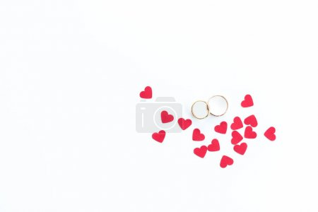 Photo for Top view of golden wedding rings and pink hearts symbols isolated on white, wedding rings background - Royalty Free Image