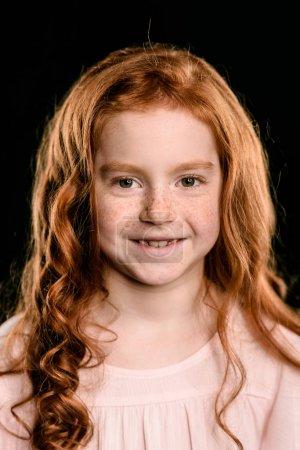 Photo pour Portrait de l'adorable rousse souriant et regardant la caméra isolée sur fond noir - image libre de droit