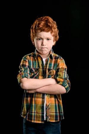 Photo pour Portrait de garçon adorable rousse avec les bras croisés en regardant la caméra isolée sur fond noir - image libre de droit
