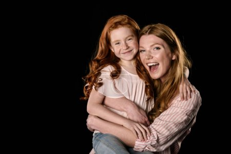 Photo for Beautiful redhead mother and daughter having fun together isolated on black - Royalty Free Image
