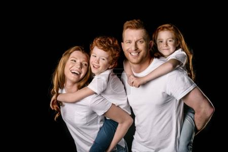 Photo for Happy redhead family in white t-shirts smiling isolated on black - Royalty Free Image
