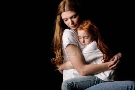 Photo for Mother and little daughter hugging each other isolated on black - Royalty Free Image