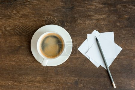 Photo for Top view of blank papers with pencil and cup of coffee on wooden table top - Royalty Free Image