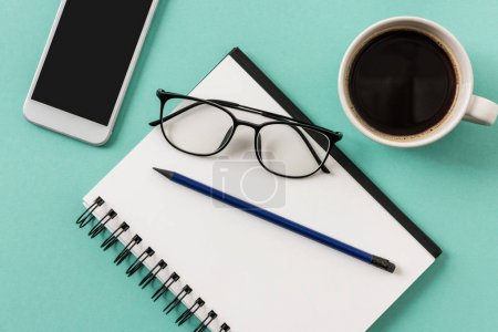Photo for Top view of notebook with cup of coffee and smartphone with glasses mock-up, small office home office - Royalty Free Image
