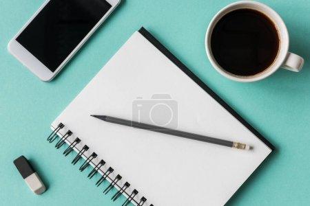 Photo pour Vue du haut du bloc-notes avec tasse de café et smartphone avec maquette de lunettes, petit bureau à domicile - image libre de droit