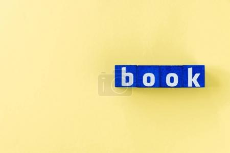 Photo for Book word made from blue cubes on yellow surface - Royalty Free Image