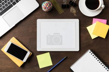 Photo for Top view of tablet and other digital devices on home office table - Royalty Free Image