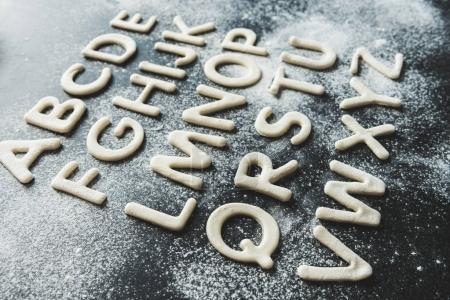 Photo for Close up of dough for cookies in forms of letters with powdered sugar, cookie dough - Royalty Free Image