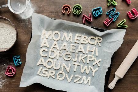 cookies in forms of letters with rolling pin