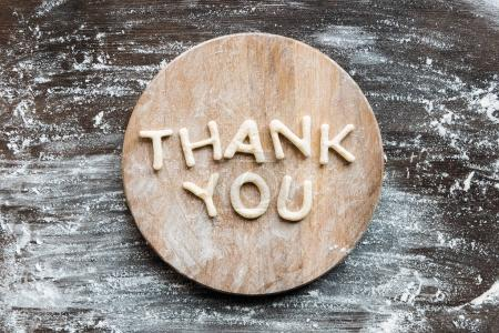 Photo for Top view of lettering thank you made from cookie dough with flour on wooden cutting board - Royalty Free Image