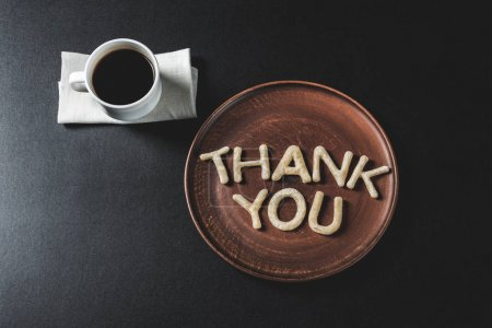Photo for Top view of lettering thank you made from cookie dough on wooden plate with coffee cup - Royalty Free Image