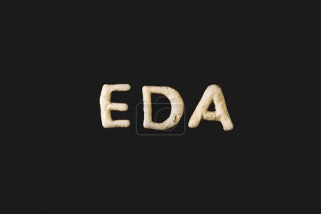 Photo for Top view of word eda made from cookie dough isolated on black - Royalty Free Image
