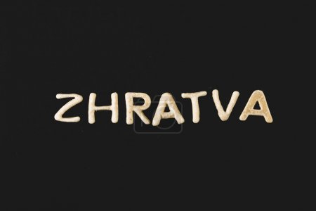 Photo for Top view of word zhratva made from cookie dough isolated on black - Royalty Free Image