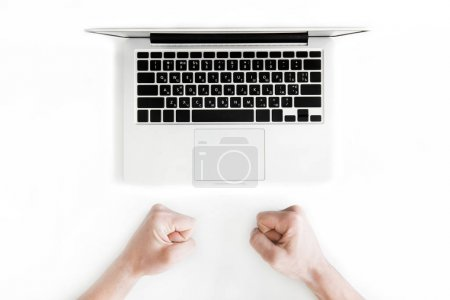 Photo for Top view of human fists and laptop computer isolated on white, wireless communication concept - Royalty Free Image