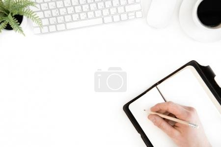 Photo for Top view of person writing in diary at workplace with computer keyboard, isolated on white - Royalty Free Image