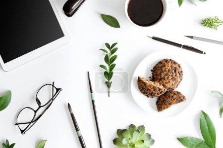 Photo pour Vue de dessus de tablette numérique, cookies et fournitures de bureau isolés sur blanc, concept de communication sans fil - image libre de droit