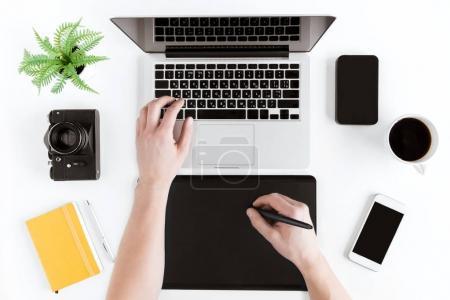 Photo pour Vue du haut des mains en utilisant une tablette graphique et un ordinateur portable sur le lieu de travail - image libre de droit