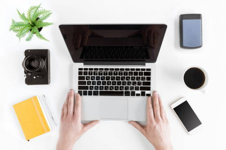 Photo for Top view of hands holding laptop on modern workplace with coffee cup - Royalty Free Image