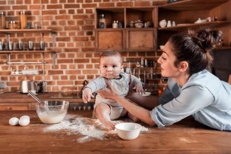 Photo for Happy mother with her son preparing dough for cookies and having fun together at the kitchen - Royalty Free Image