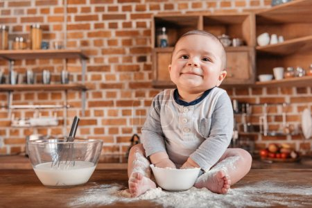 Photo for Happy little boy playing with flour and sitting on kitchen table. Domestic life concept - Royalty Free Image