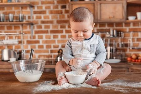 Photo for Adorable little boy playing with flour and sitting on kitchen table. Domestic life concept - Royalty Free Image