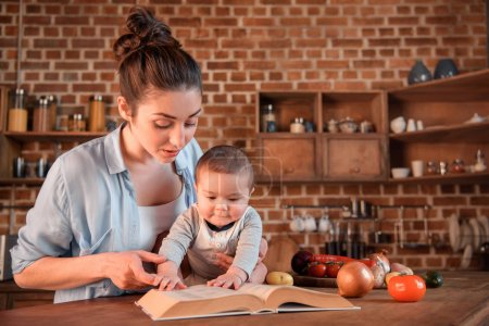 Photo for Mother with her baby son reading recipe book before preparing dinner in the kitchen - Royalty Free Image