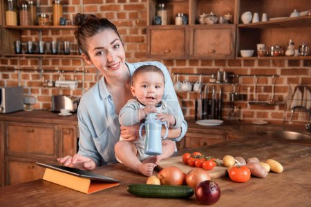 Photo for Portrait of young mother with her little son cooking dinner together and using digital tablet in the kitchen - Royalty Free Image