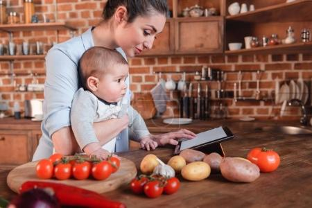 Photo for Mother with her baby son looking for recipe on digital tablet before cooking dinner in the kitchen - Royalty Free Image