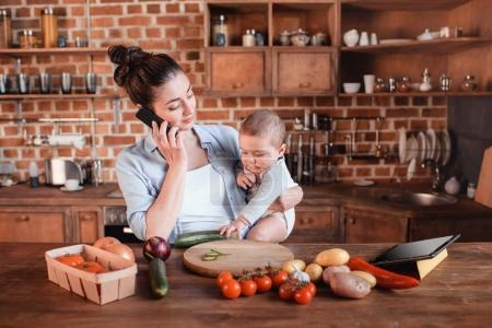 Photo for Portrait of mother with son talking on smartphone and preparing dinner in the kitchen - Royalty Free Image
