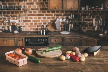 Photo for Kitchen table with variety of raw vegetables, chopping board and digital tablet ready for preparing breakfast - Royalty Free Image