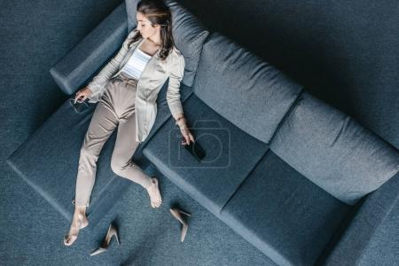 Tired businesswoman resting on couch