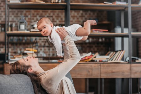 Photo for Side view of cheerful mother and baby boy having fun together at home - Royalty Free Image