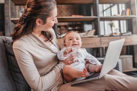 Photo for Young mother with her adorable son using laptop together on the couch. Domestic life concept - Royalty Free Image
