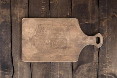 Photo for Top view of old scratched chopping board on kitchen table - Royalty Free Image