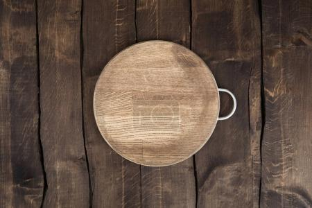 Photo for Top view of scratched circular chopping board on wooden background - Royalty Free Image