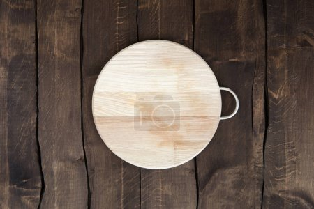 Photo for Top view of new circular wooden chopping board on wooden background - Royalty Free Image