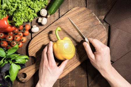 hands cutting pepper on chopping board