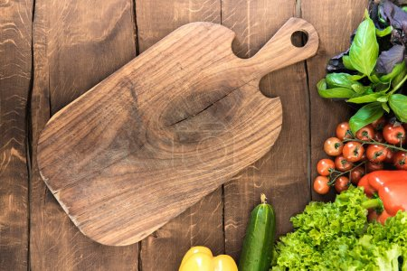 Photo for Top view of vegetables and greens with wooden cutting board. Healthy food background - Royalty Free Image